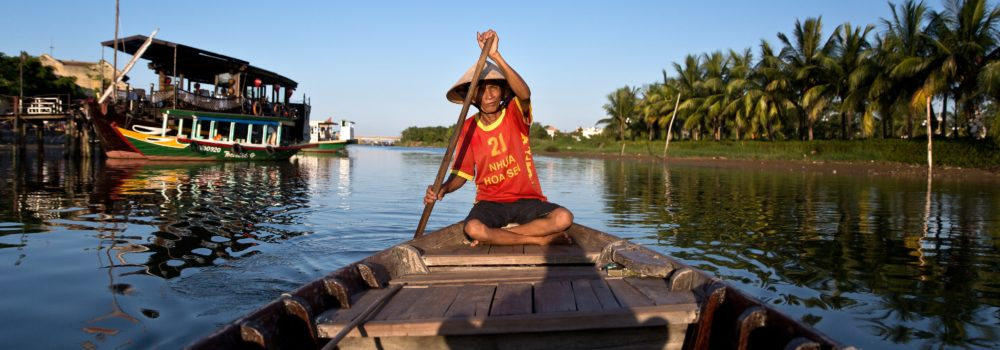 In this picture taken on June 28, 2015 a man paddles his boat along the Thu Bon river in Hoi An, Vietnam's central Quang Nam Province. The old town area of Hoi An, a well-preserved example of a traditional Asian trading port, is recognized as a UNESCO World Heritage Site and is a popular travel destination for local and international tourists. AFP PHOTO / DALE DE LA REY        (Photo credit should read DALE de la REY/AFP/Getty Images)